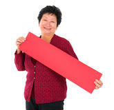 Chinese senior woman with red spring couplets Stock Images