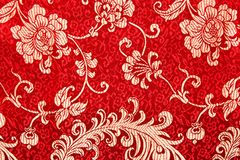 Chinese shiny ornament on red fabric. Flowers and characters Royalty Free Stock Photos