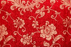 Chinese shiny ornament on red fabric. Flowers and characters Royalty Free Stock Image