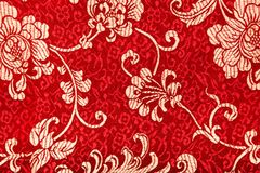 Chinese shiny ornament on red fabric. Flowers and characters Stock Photo