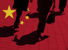 Chinese shoppers. Silhouetted pedestrians overlaid with Chinese flag Stock Images
