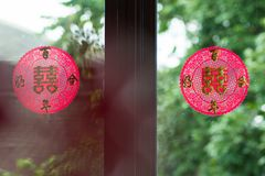 Chinese sign tear on glass door, translate: double happiness. Whenever Chinese people see this symbol, they would think of a wedding that two persons are Stock Photo