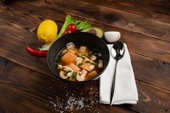 Chinese soup with red fish in a black plate on a wooden background royalty free stock image