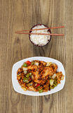 Chinese Spicy Chicken Dish with Rice in bowl on faded wood Royalty Free Stock Image