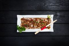 Chinese spicy meat salad. With chopsticks on white crockery, wooden background with top view Stock Image