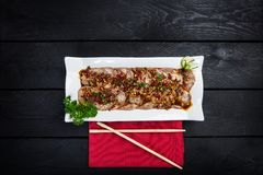 Chinese spicy meat salad. On white crockery with chopsticks, wooden background with top view Royalty Free Stock Photo