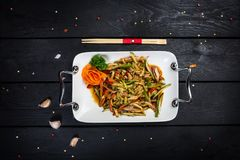 Chinese meat salad with cucumber. Chinese spicy meat salad on white plate, with chopsticks. Wooden black background with top view Royalty Free Stock Photos