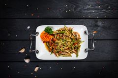 Chinese meat salad with cucumber. Chinese spicy meat salad on white plate, with cutlery. Wooden background with top view Royalty Free Stock Images