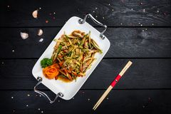 Chinese meat salad with cucumber. Chinese spicy meat salad on white plate, served with chopsticks. Black wooden background with top view Royalty Free Stock Photography