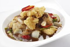Chinese spicy noodles topped with crispy fish in gravy Stock Image