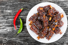 Chinese spicy Spare Ribs on white dish sprinkled with sesame Stock Photos