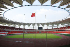 A chinese stadium. A modern stadium in China with Chinese flag in the blue sky Royalty Free Stock Images