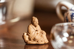 Chinese statue on the wooden table. Figure of chinese old man Royalty Free Stock Photo