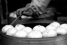 Chinese steamed buns. A black and white image of a vendor's hand, holding a pair of chopsticks and using it to get a Chinese steamed bun (called Bao Stock Photos
