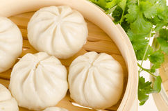 Chinese steamed buns in bamboo steamer basket with cilantro on w Stock Photo
