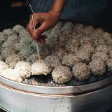 Chinese steamed meatballs covered with rice. Picking up hot steamed traditional Chinese rice meat balls with a stick Stock Images