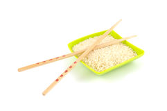 Chinese sticks on green bowl with rice. Chinese sticks on bowl isolated on white background Royalty Free Stock Photo
