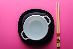 Chinese sticks white plate on a pink background royalty free stock image