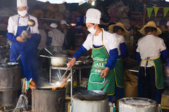 Chinese Stir Fry. Chefs work frying chicken at a big restaurant booth at the Third Month Fair, a 5,000 year old fair in Dali, Yunnan province, China Royalty Free Stock Photo