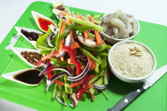 Chinese stir fry ingredients mix. A mixture of chinese sauces  cut vegetables rice and prawns displayed on a green board Royalty Free Stock Photos