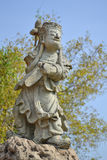 Chinese stone sculpture. Broken Chinese stone sculpture stands on rock Stock Images