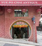 Chinese Store with Round Doorway. A traditional style doorway entrance to Yue Po Antique Shop with a Merry Christmas banner, across the street from Man Mo Temple Stock Images