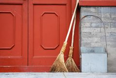 Chinese straw brooms. Some straw brooms leaning against a red door, China stock image