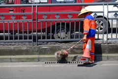 Chinese worker sweeping street on a busy road in China. Chinese street sweeper working on a busy road in China as cars pass by Royalty Free Stock Photos