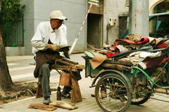 Beijing, China - June 10, 2018: Chinese elderly man repairs shoes on the street of Beijing. stock photos
