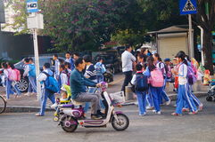 Chinese students home after school through traffic intersection Royalty Free Stock Photos