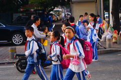 Chinese students home after school through traffic intersection Royalty Free Stock Image