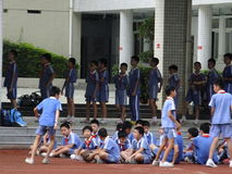 Chinese students are sitting on the ground, in the physical education class Stock Photography