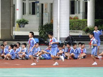 Chinese students are sitting on the ground, in the physical education class Royalty Free Stock Photos