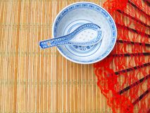 Chinese style background. Chinese patterned porcelain soup plate with spoon, on a bamboo placemat. Red lacy fan in the background. Empty space for the text stock images