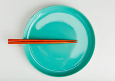 Chinese style chopsticks put on green dish Royalty Free Stock Image