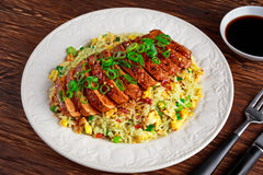 Chinese style Egg fried rice with sliced pork fillet on wooden table. Royalty Free Stock Photo
