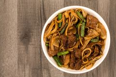 Chinese Style Fried Beef And Mushrooms Noodles. Against A Dark Wooden Table Top royalty free stock image