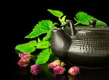 Chinese style tea. With mint and dry roses on black Royalty Free Stock Photo