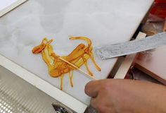 Chinese sugar painting. Chinese entertainer painting with hot maltose, xiamen city, china. animal like sheep, goat, deer, horse or elk Royalty Free Stock Images
