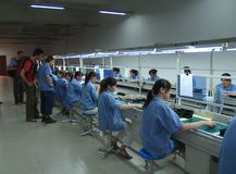 Chinese sweatshop interior. Interior view of a Chinese electronics assembly factory with girls working and manufacturing parts Stock Image