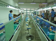 Chinese sweatshop interior. Interior view of a Chinese electronics assembly factory with girls working and assembling parts Stock Photos