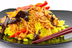 Chinese sweet and sour chicken. With rice on black plate stock photos