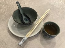 Chinese Tableware. Typical Chinese tableware in Chinese restaurant including a pair of chopsticks and a spoon Stock Photo