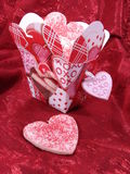 Chinese take out box of heart sugar cookies. Heart shaped sugar cookies in a heart decorated chinese take out box. Red fabric background Stock Image