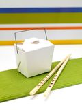 Chinese Takeaway. Chop sticks and a takeaway box on a kitchen bench Royalty Free Stock Photography