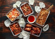 Chinese takeaway food. Crispy shredded beef, sweet and sour chicken wings, egg noodles with bean sprouts, pineapple. Chilli dip and prawn crackers stock image