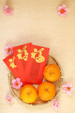 3 Chinese tangerines in basket with Chinese New Year red packets - Series 4 Stock Images