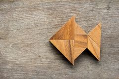 Chinese tangram puzzle in fish shape on wood background royalty free stock photography