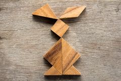 Chinese tangram puzzle in rabbit shape on wood background Con stock photography