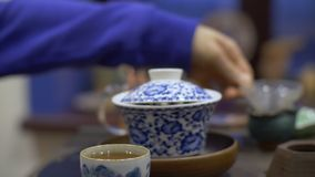 Chinese tea ceremony with hot aromatic drink. Chinese tea ceremony. Close up of traditional chinese pot and cup with hot natural aromatic tea stock video footage